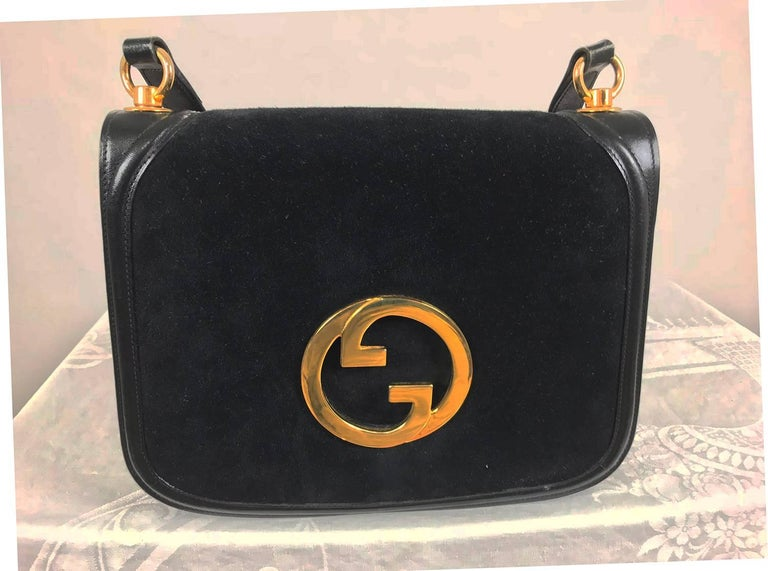Gucci black suede and leather Blondie shoulder bag from the 1970s with gold hardware. Iconic bag of deep black suede trimmed in black leather with a black leather adjustable shoulder strap. The flap front bag features a large gold metal Gucci logo