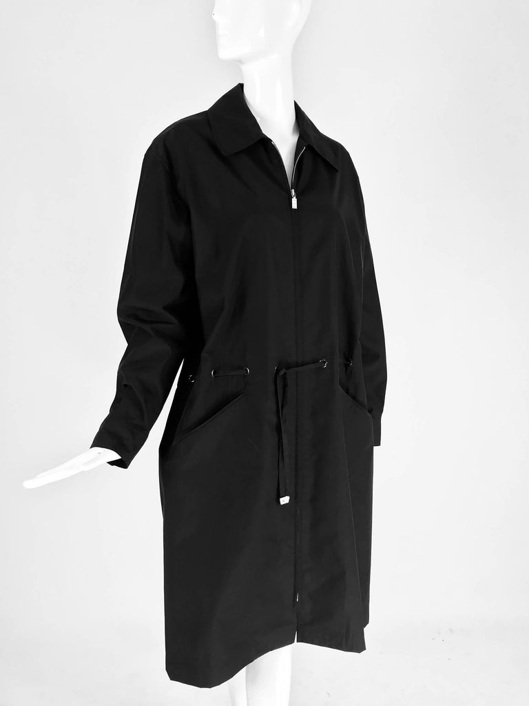 Chanel black zip front draw cord waist rain coat 1998P.  Stylish raincoat fabric is cotton with spandex and polymide, feels like mid weight nylon. Zip front coat has collar and a draw cord waist that ties at the front with silver logo tab ends. Yoke