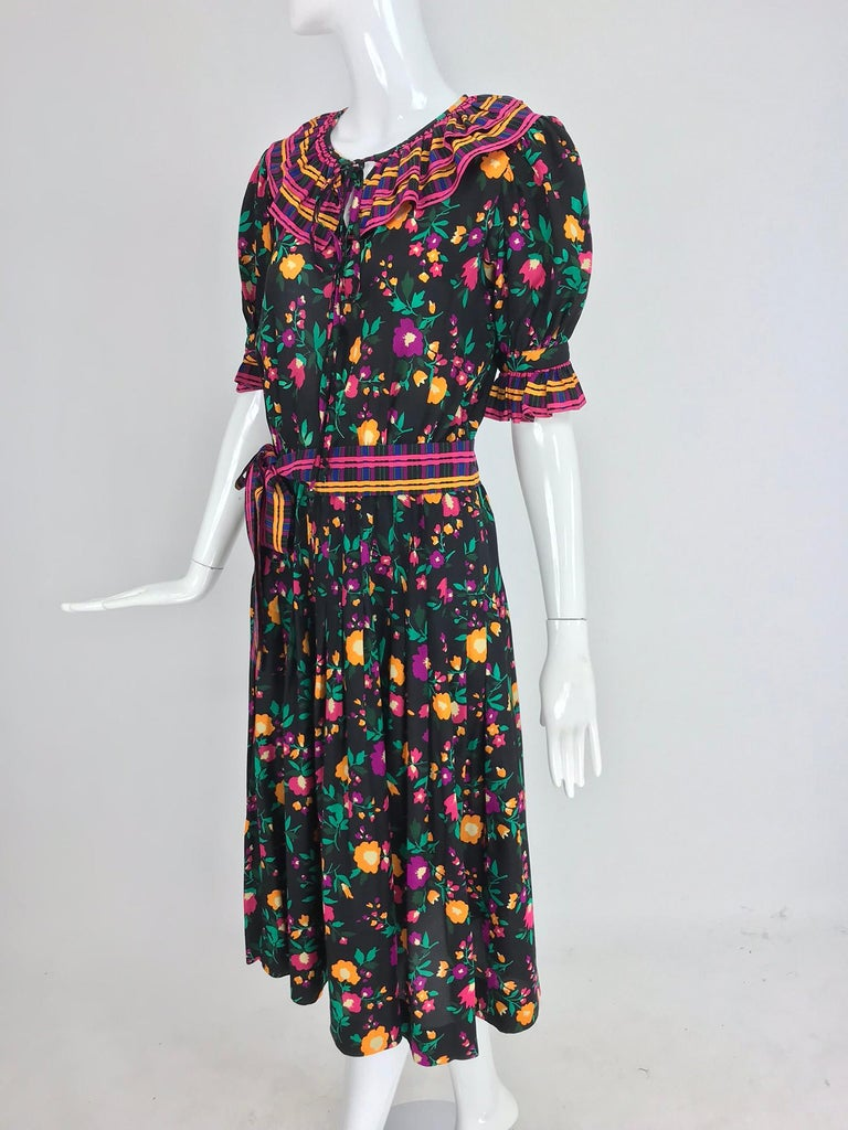 Yves Saint Laurent Rive Gauche silk floral mix print dress from the 1970s. Vibrant floral print set on a black ground with coordinating stripes make this eye catching dress perfect for anytime you want to look fabulous. Pull on dress has a peasant