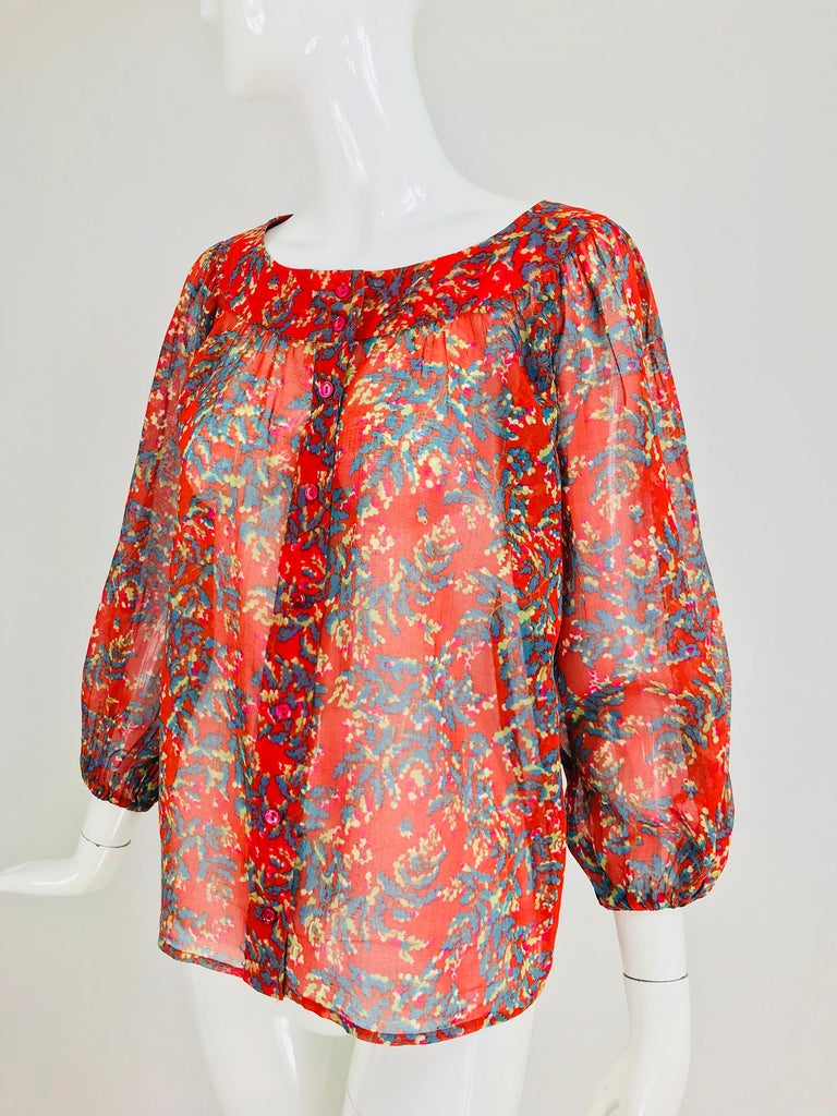 Yves Saint Laurent sheer floral cotton blouse from the 1970s. Peasant style blouse of sheer cotton voile, the banded neckline has light gathering with a full body, 3/4 length full raglan sleeves with cased elastic cuffs. The blouse closes at the