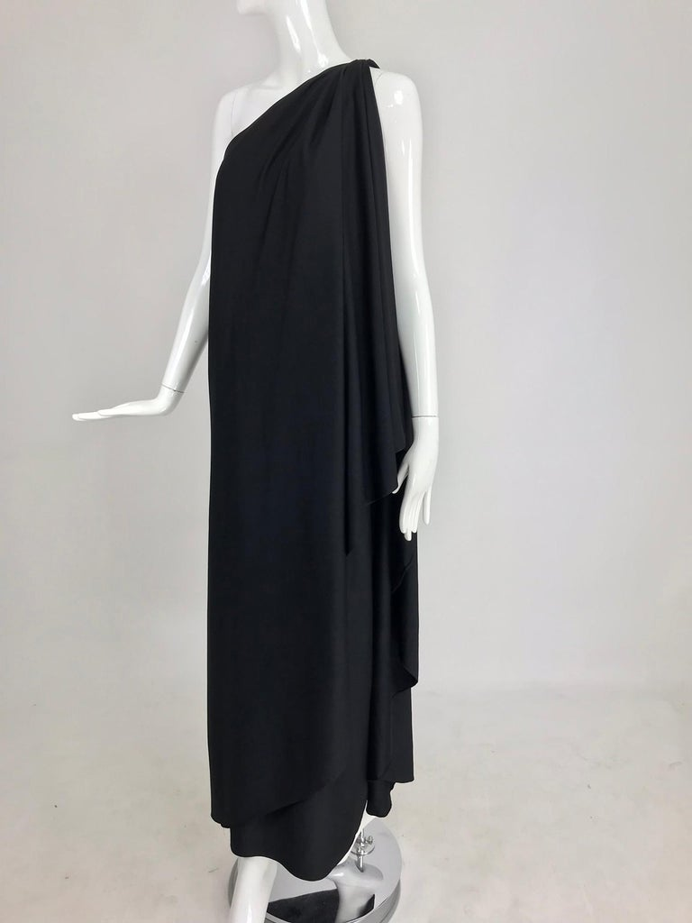Halston IV one shoulder black jersey draped maxi dress from the 1980s. Goddess style gown closes at the draped shoulder with a hidden hook and eye, the gown wraps and drapes and is open at the side front. Side hem vent. Black poly jersey fabric