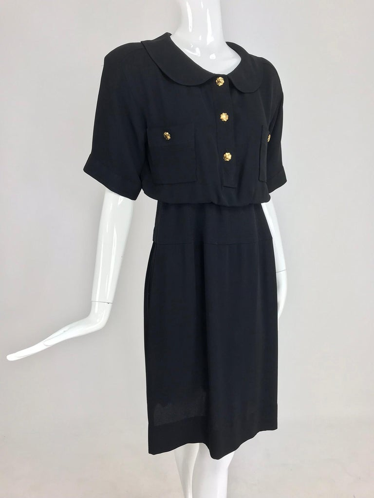 Chanel vintage black crepe shirtwaist day dress. Classic shirtwaist style dress with cuffed, short sleeves, round collar at the neckline, button front bust patch pockets and button front with gold Chanel 4 leaf clover buttons, the dress has a cased