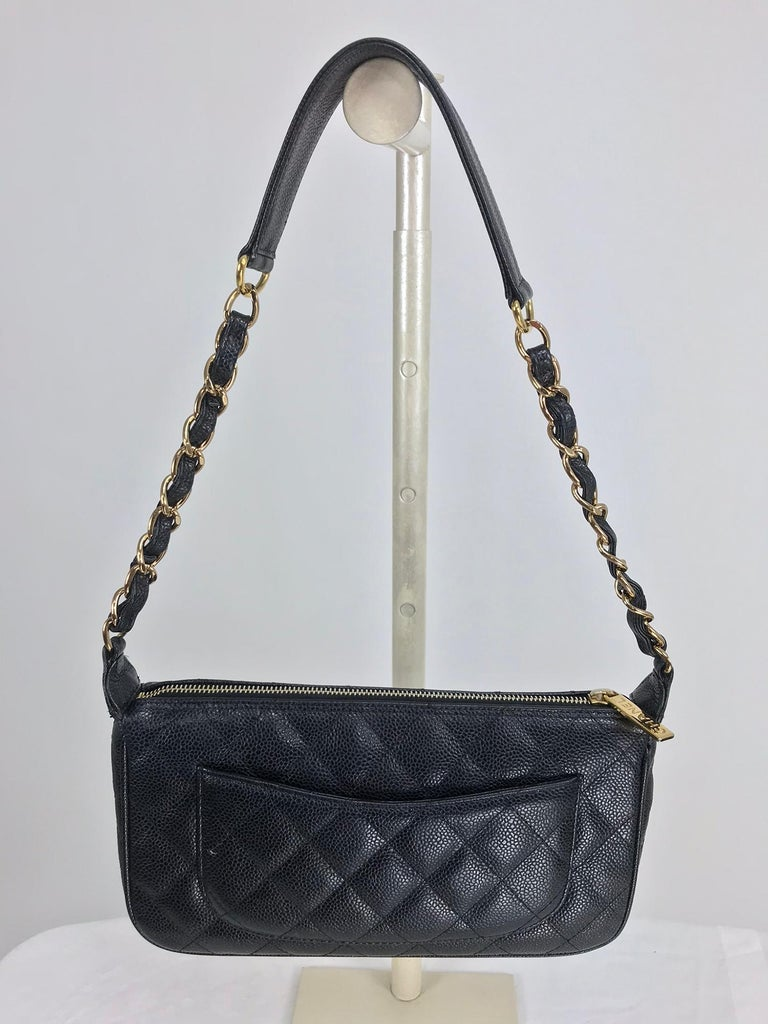 Chanel black caviar leather baguette style shoulder bag 2004-2005. Zipper top bag with gold metal Chanel zipper pull, chain handle with caviar leather top shoulder top. Intertwined Chanel C's at the front, outside slip pocket at the back. Interior