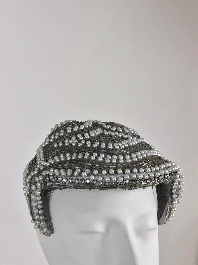 Designed by Lora silver beads and pearl cocktail hat 1950s. This beautiful hat fits like a wide head band, it is hand made of sliver satin and covered with silver tube beads and white pearls. Fully lined in lace. In excellent barely worn