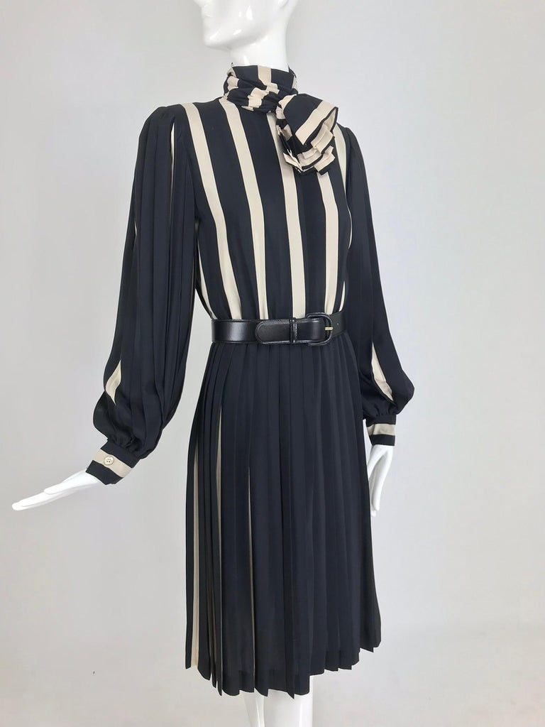 Bill Blass pleated silk black and tan stripe dress from the 1970s. Shirtwaist style dress features long full pleated sleeves with banded cuffs that close with buttons. The dress closes at the front with hidden buttons, there is an attached neck wrap