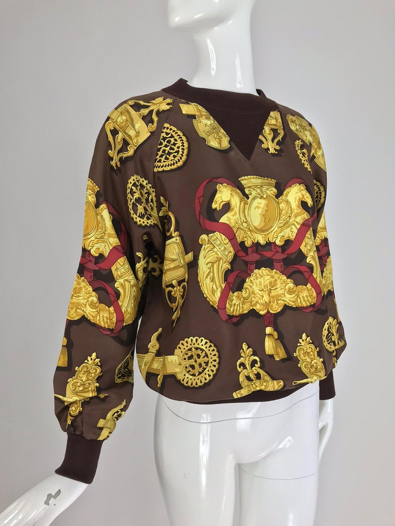 Hermes Ferronnerie Silk Twill Wool Knit Trim Shirt Sweater Caty Latham from the late 1970s. Pull on shirt or sweater is made from Hermes silk twill fabric in the ferronnerie pattern designed by Caty Latham. The top has wool knit collar, cuffs and