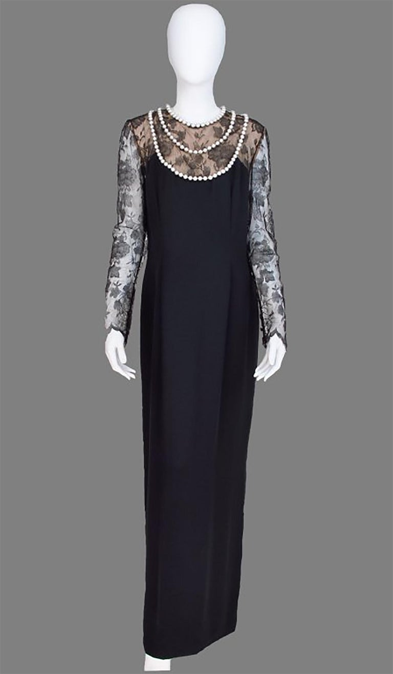 Bill Blass black lace and black silk chiffon gown with pearl applique necklace from the 1970s. Chic column gown of lustrous black silk, the upper bodice and sleeves are delicate black lace, the bodice is lined with nude silk, the neckline is