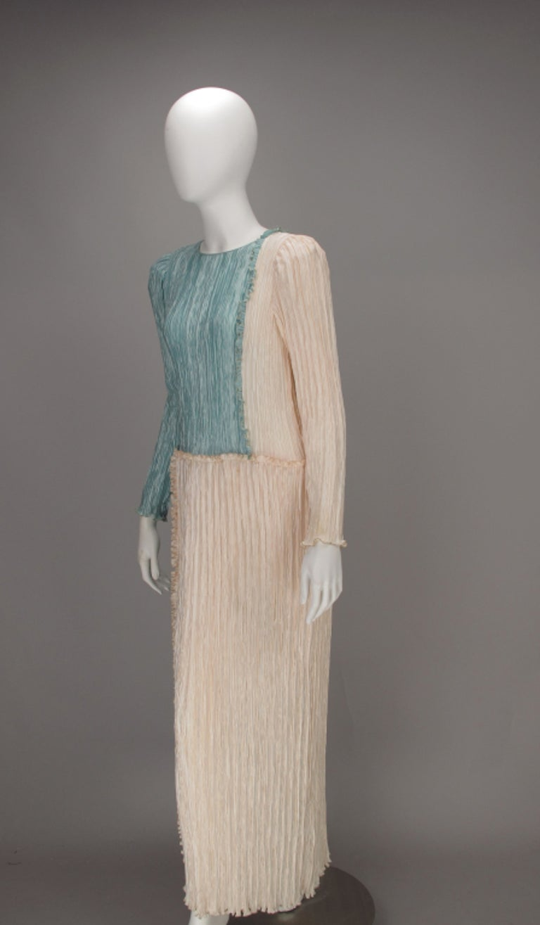 Mary McFadden Pleated Fourtuny Style Colour Block Gown from the 1980s. This beautiful gown is done in a blocking grid in French blue and cream, with narrow ruffles, that are gold thread edged. The gown has long sleeves, it ties at neck back and
