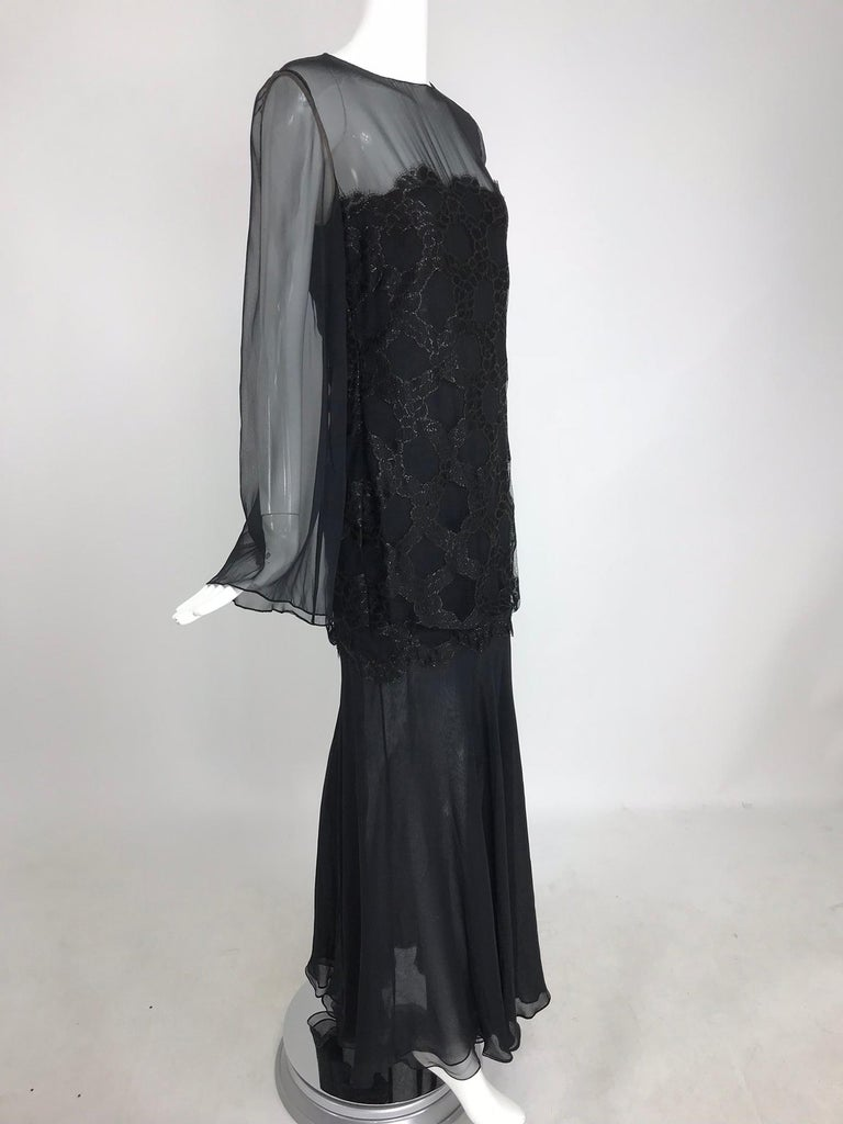 Bill Blass lacquered lace black silk chiffon evening dress from the 1970s. This beautiful evening gown has never been worn and still has the original tags. Jewel neckline dress has long sheer bell sleeves, the bodice, through the bust to the hip has