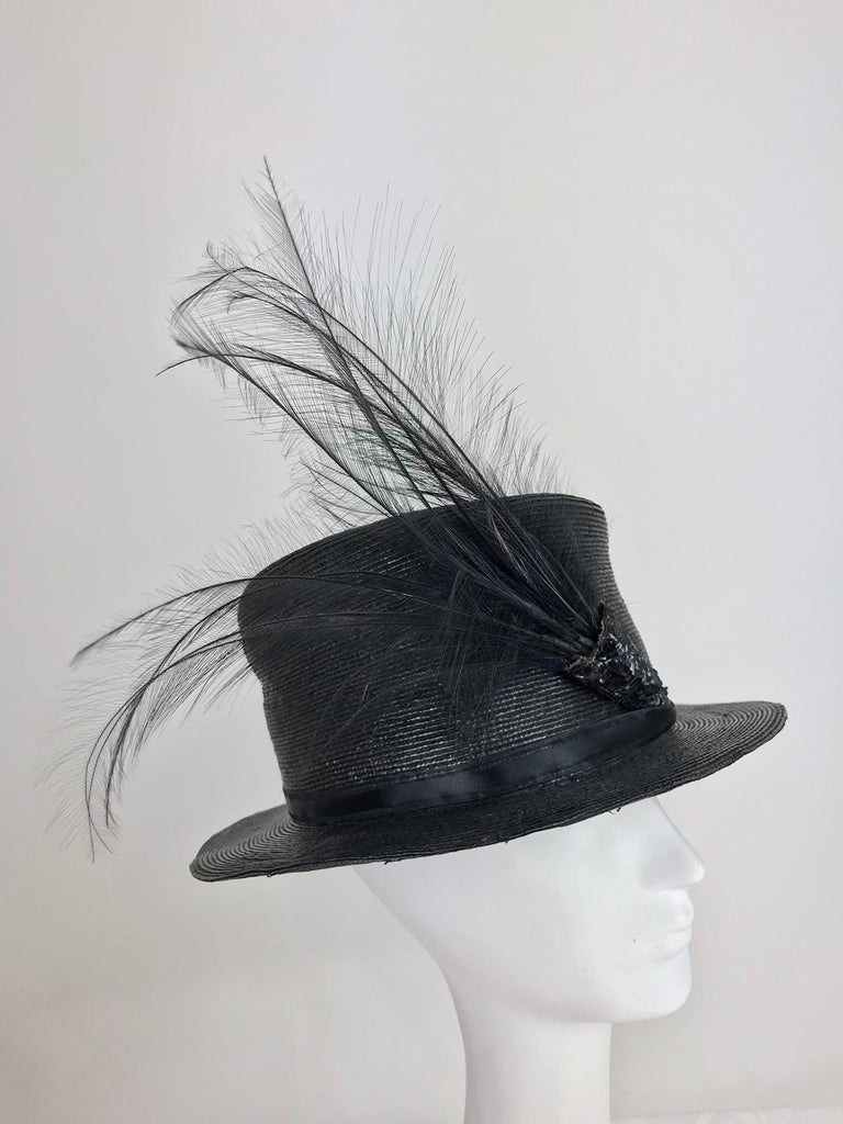 Edwardian Glazed black straw hat with Bird of Paradise feathers. Tall crown hat with a narrow brim is made from a fine black glazed straw. The hat has a narrow ribbon band (replaced) with the original black sequin decoration that holds the plume of