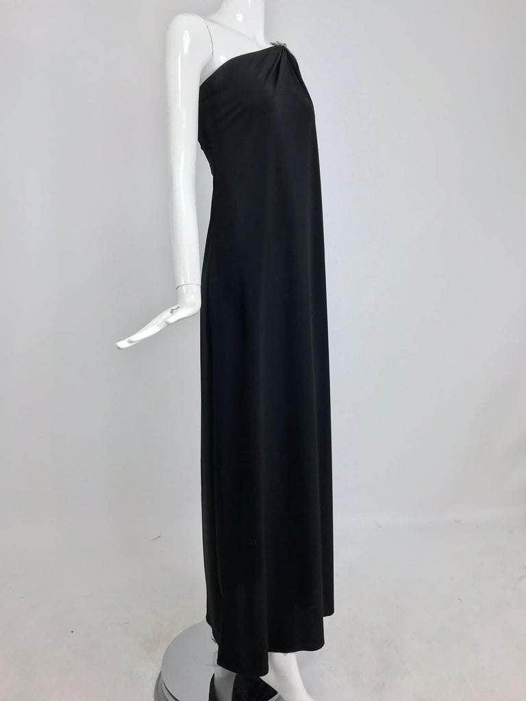 Adele Simpson black jersey one shoulder gown with jewel clasp. This sleek gown is simple and elegant, the fabric is gathered at the shoulder into a rhinestone clasp and drapes from the shoulder across the bust and falls full to the hem, there is a