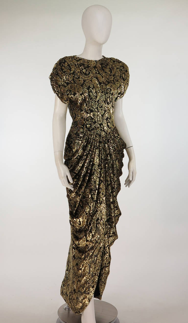 1940s inspired evening gown in black & gold chiffon and Lurex. A statement making dress from the 1980s from Lillie Rubin. Padded shoulders with a bodice that is fitted through the waist, the back of the dress closes with covered button & loops, a