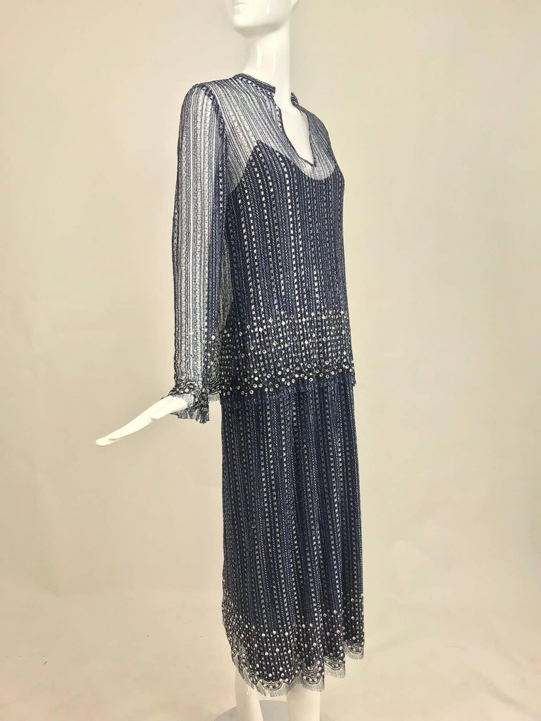 Beautiful lacy sheer inky blue and silver metallic fabric with bands of glittering prong set rhinestones at the cuffs and hem of the tunic and hem of the dress. Labeled Mollie Parnis and from the 1970s. Two piece tunic and dress. The under dress has