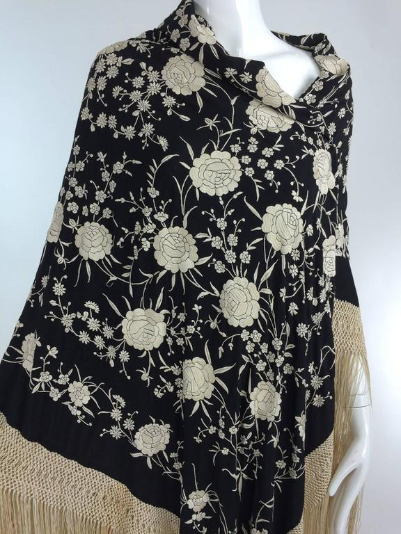 Black & white floral silk Hand Embroidered Canton Piano Shawl 1920s...Black silk shawl is heavily hand embroidered in satin sticth with large and small white peony's or roses with trailing leaves and vines...There is a deep macrame border and fringe