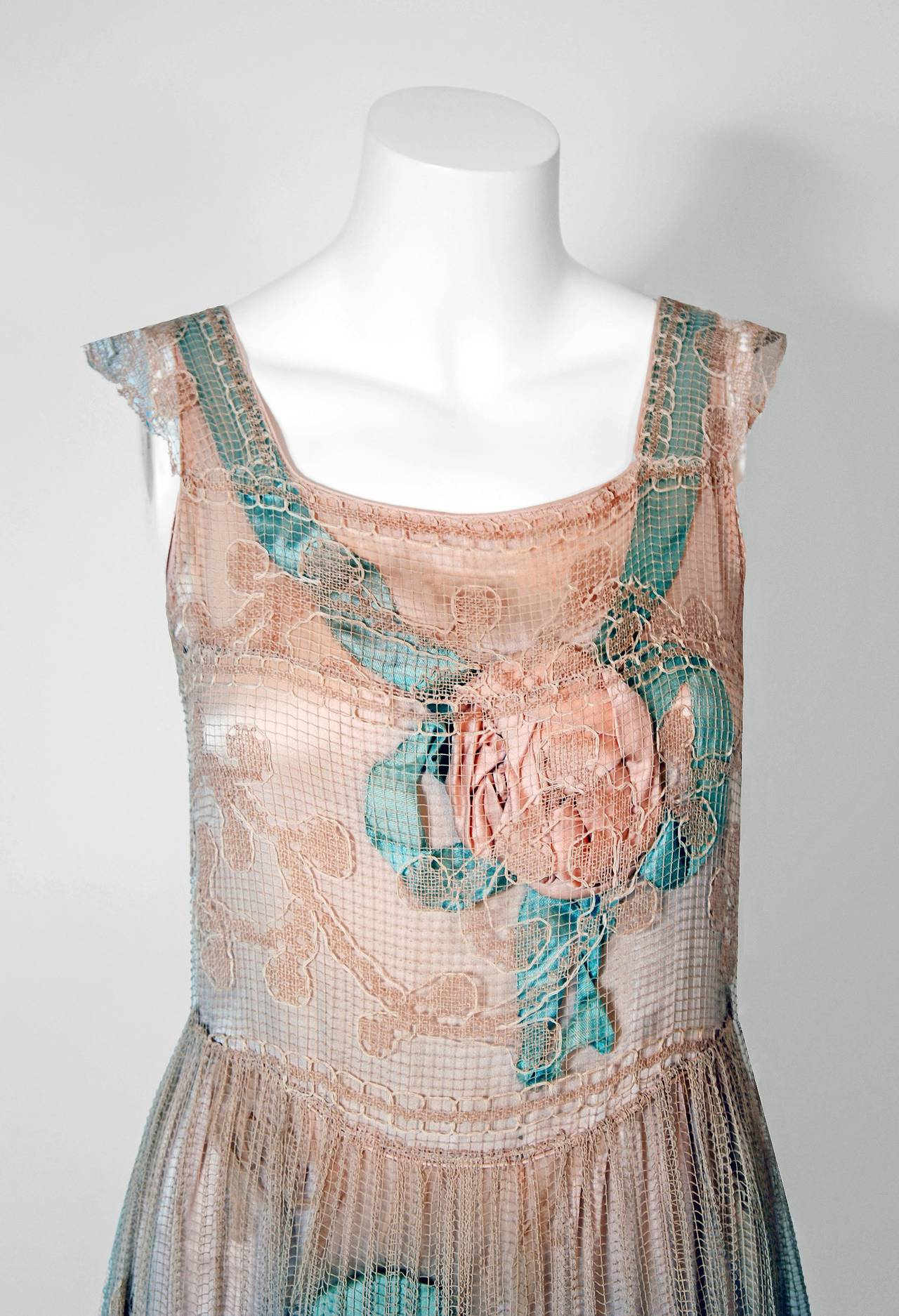 Breathtaking 1920's museum quality dress with two layers cleverly designed to complement each other; a fine filet-lace outer layer with a foliate design over an ecru silk-crepe slip layer embroidered with pastel silk-ribbon rosettes.  The rosettes