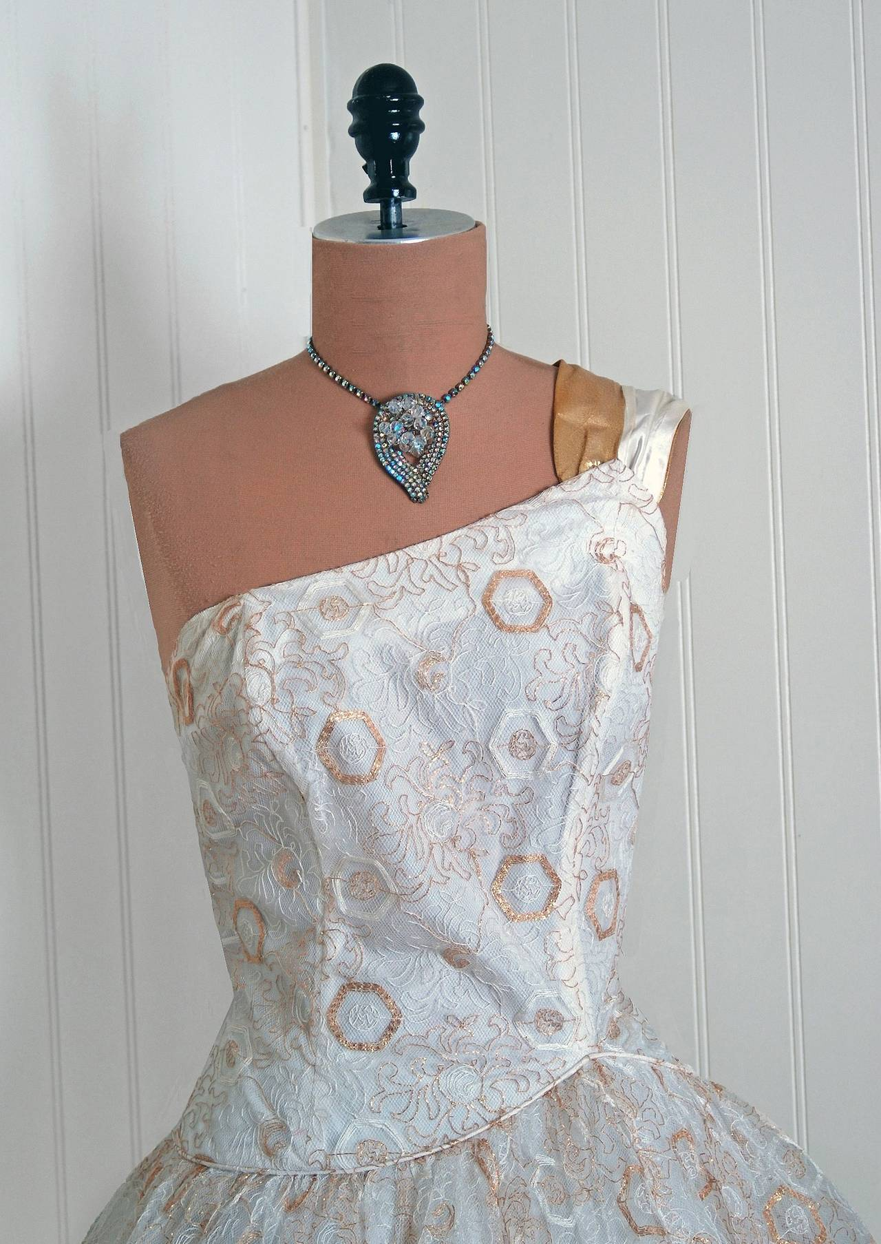 """With its metallic-gold embroidered sparkle and flawless """"new look"""" silhouette, this Emma Domb designer party dress has the casual elegance the 1950's were known for. The artisanship alone is unbelievable. A stunning atomic deco pattern embroidered"""