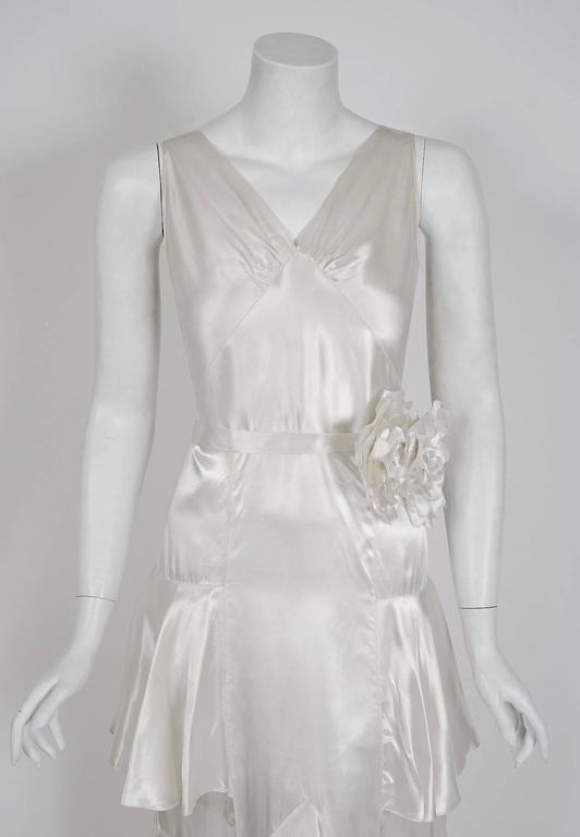 "A stunning ivory white shimmer silk-satin gown from the ""Old Hollywood"" era of glamour. The bodice is a low-cut plunge sleeveless with seductive bias-cut construction. I adore the floral applique belted nipped waist which adds the perfect amount of"