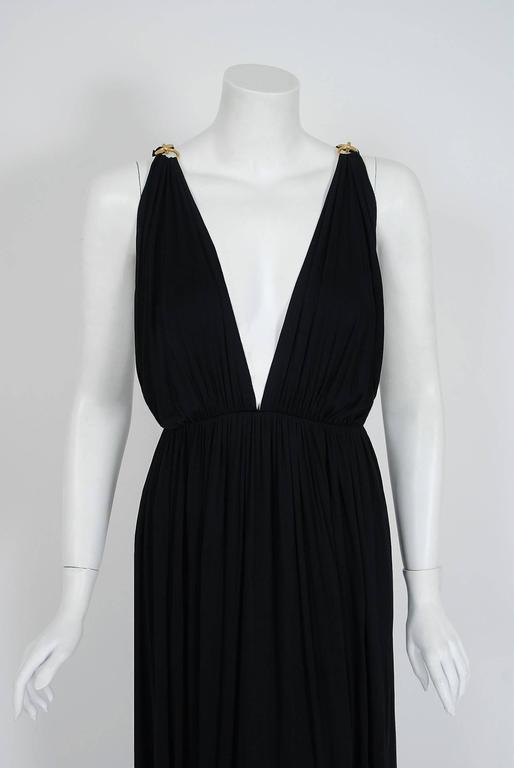 Seductive black rayon-jersey evening gown from the infamous Yves Saint Laurent Rive Gauche collection of 1977. Pieces from this decade are very rare and are true examples of fashion history. I love the breathtaking gold hardware links plunging