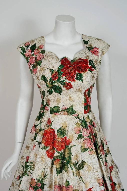 This beautiful metallic hand-painted cotton sundress by Kramer is the perfect addition to any summer wardrobe. With its vivid rose-garden floral print and flawless styling, this garment has the casual elegance the 1950's were known for. The low-cut