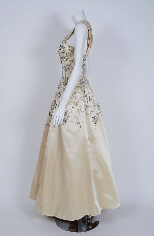 Breathtaking mid-1950's ivory silk satin ballgown attributed to Pierre Balmain. This iconic designer created a very sculptural quality which was always allied with a ladylike essence. His garments have a body and a shape of their own. This