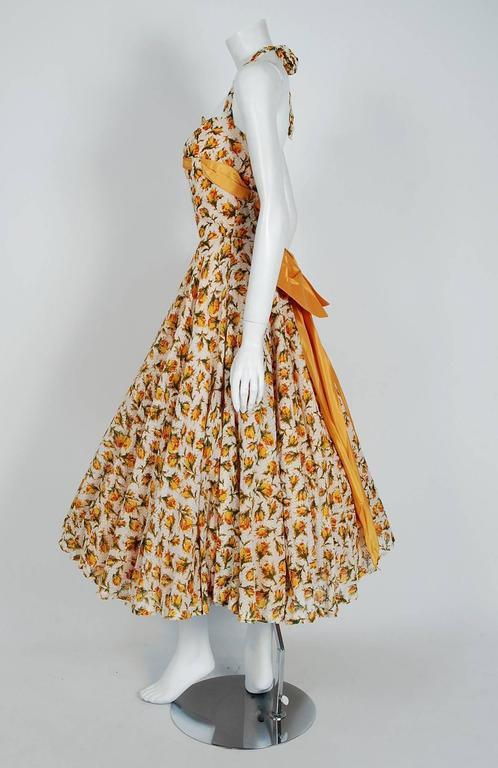 An amazing and highly stylized 1950's sundress by Lilli Diamond. With its gorgeous marigold-yellow roses floral print and flawless styling, this garment has the casual elegance the 1950's were known for. The low-cut scalloped plunge halter bodice is