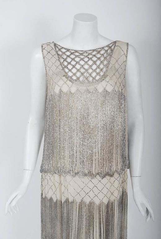 Romantic flapper dresses from the early 20th century are perennial favorites and this one is a show-stopper! The garment's simple unstructured style is so modern; the fine beadwork is a treasure trove of needle art. This beauty, fashioned from