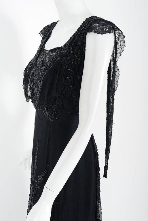 Undiminished by time, this antique evening gown still casts its seductive spell. An exceptional Edwardian tea-dress made of French chantilly-lace and silk lwith sheer black mesh net overlay, faceted beading and tassel applique. The breathtaking