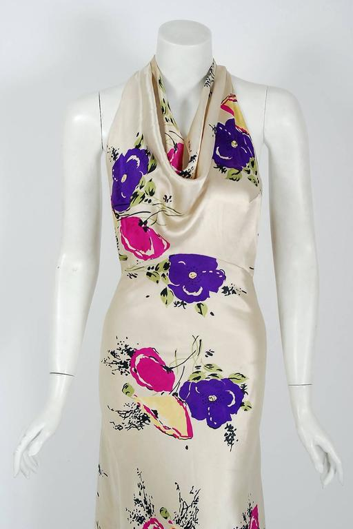 """A rare luxurious floral-garden print silk satin gown from the """"Old Hollywood"""" era of glamour. The bodice is an ultra chic cowl-neck with stylized cut-out twist backside. The waist is nipped with a tailored back belt. The lower skirt is"""