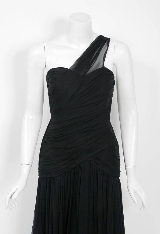 This breathtaking Adele Simpson designer gown, dating back to mid 1970's, is perhaps the most unique and flattering black dress I have ever seen. Fashioned from light-weight silk chiffon, the fabric feels like heaven against the  skin. The bodice is