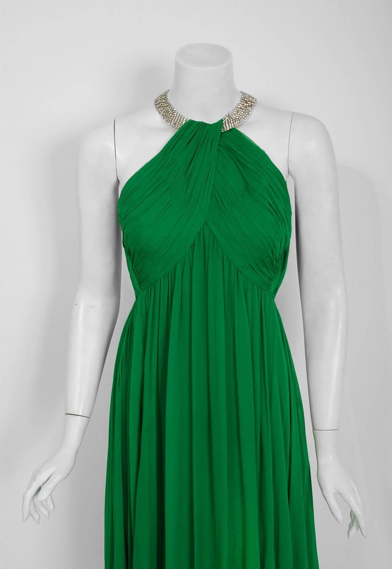 With the sparkling rhinestones and vibrant emerald-green color, this dazzling 1960's Malcolm Starr evening gown does not disappoint. The substantial weight of the layered silk-chiffon fabric whispers high-end luxury. The bodice is an elegant