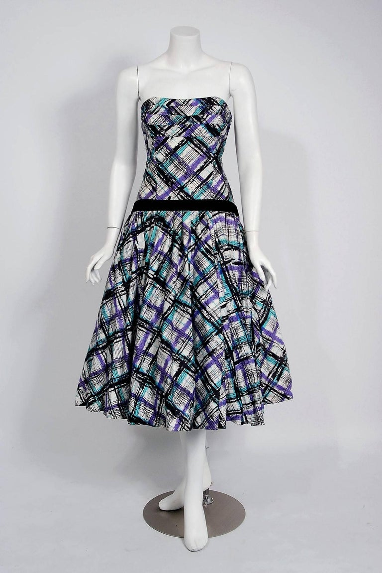 In this gorgeous 1950's graphic plaid party dress ensemble, the detailed construction and meticulous attention to detail are comparable to what you will find in modern couture. This enchanting garment is fashioned from turquoise, purple and black