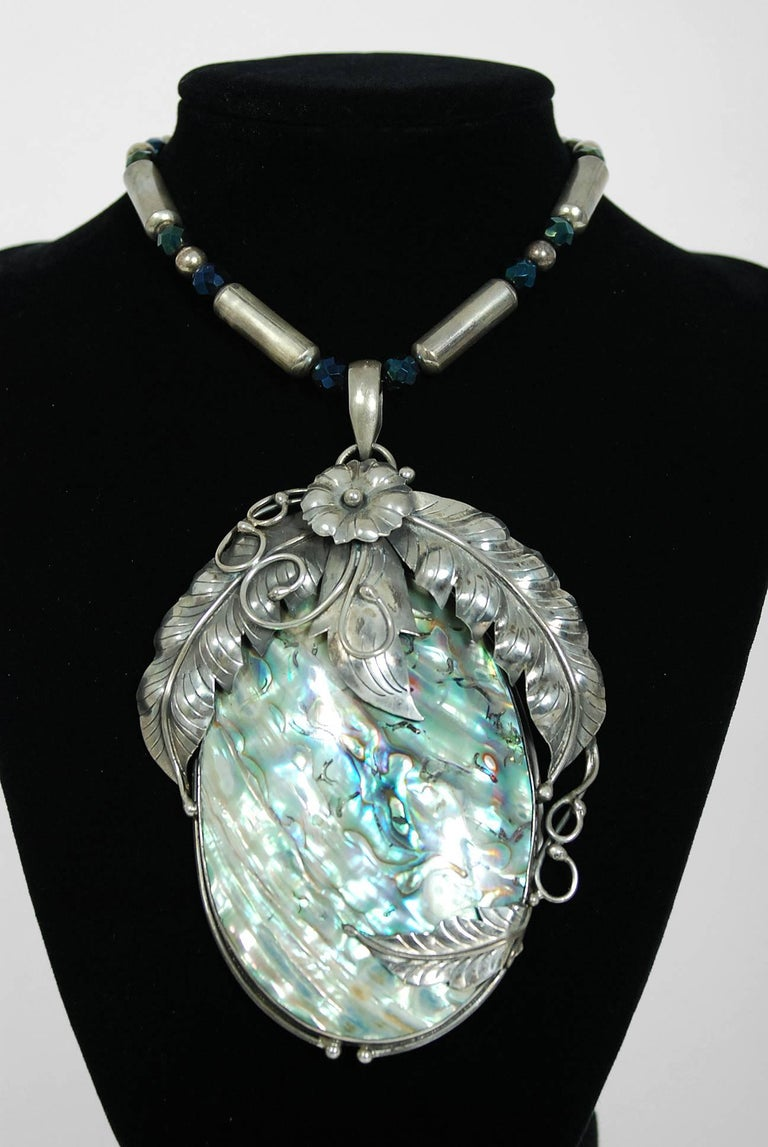 Gorgeous Native American rainbow abalone and genuine sterling silver huge statement necklace dating back to the mid 1970's. The piece has been crafted in a stunning feather motif with texture to showcase the over-sized pendant. The abalone 'sea