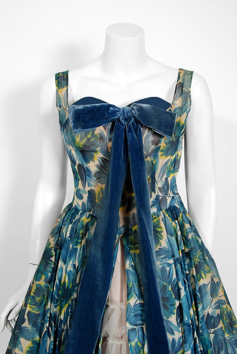 Fashioned from gorgeous blue floral-garden print organza, this 1950's Will Steinman creation has everything a woman wants. The sequin accents add the perfect amount of sparkle to the piece. The bodice has a gorgeous blue velvet boned sweetheart