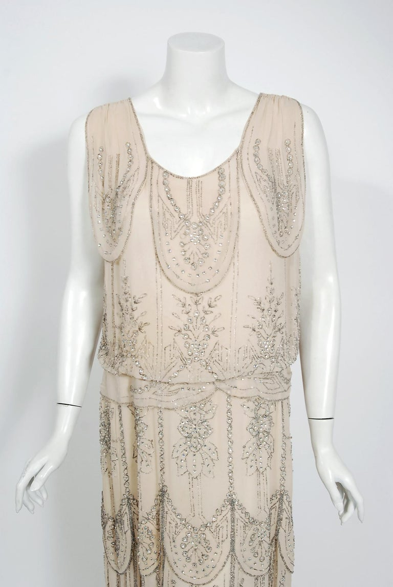 Undiminished by time, this early 1930's ivory-creme couture gown still casts its magical spell. This exceptional French beauty is fashioned in triple layered high-quality silk chiffon. It is then lavishly embellished with prong-set rhinestones and