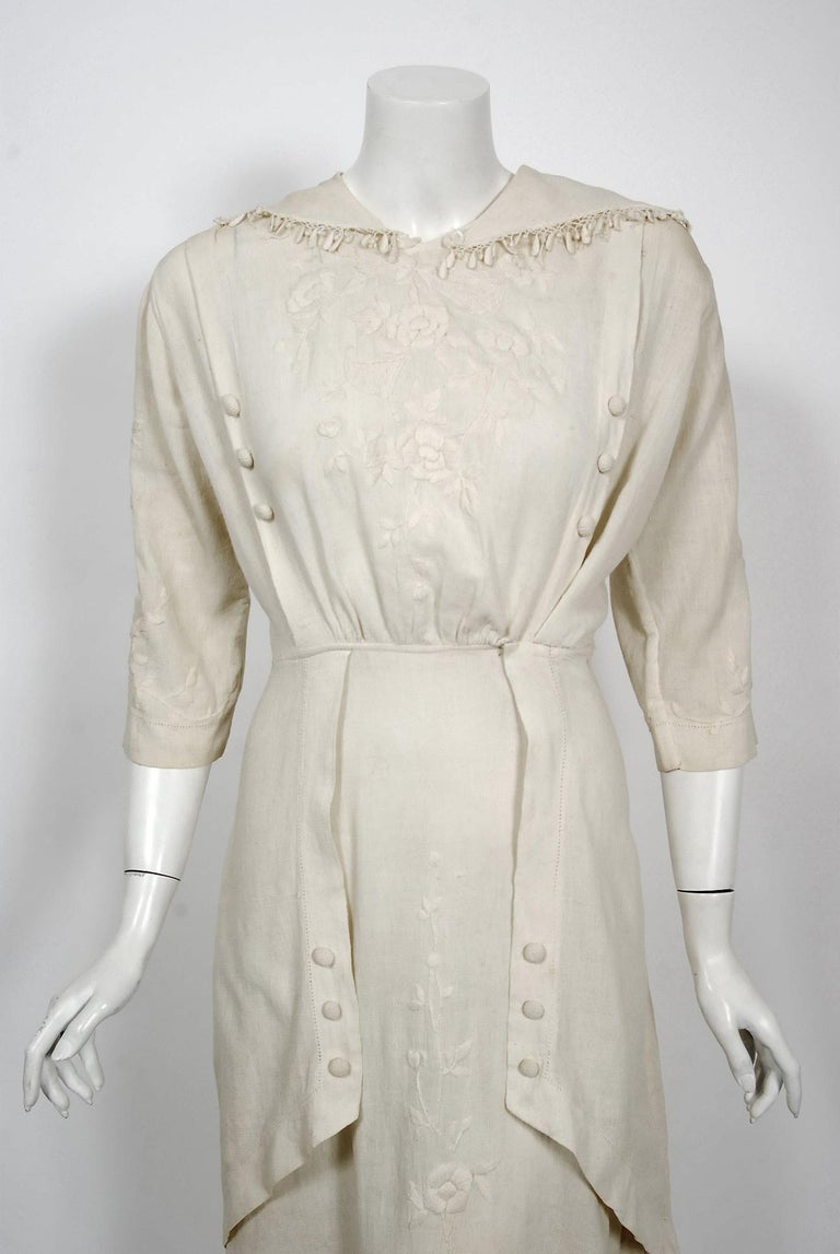 This ethereal Edwardian couture ivory silk-crepe tea gown, with an abundance of embroidery, is of the highest quality. The garment was discovered with provenance; tagged 'Bessie Andrews white crepe dress 1916'. The stylized charm of the embroidered