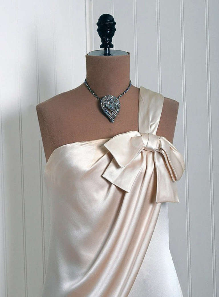 In this gorgeous 1960's ivory-creme gown, the detailed construction and meticulous attention to detail are comparable to what you will find in modern couture. This enchanting garment is fashioned from a mid-weight silk. The bodice is an alluring