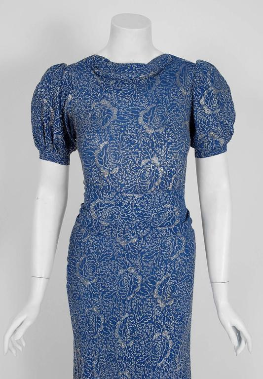 """A luxurious sapphire-blue shimmer lame gown from the """"Old Hollywood"""" era of glamour. The bodice is an elegant puff-sleeve silhouette with slight cowl neckline. The waist is nipped with a stylized wide matching sash-belt. The lower skirt is added in"""