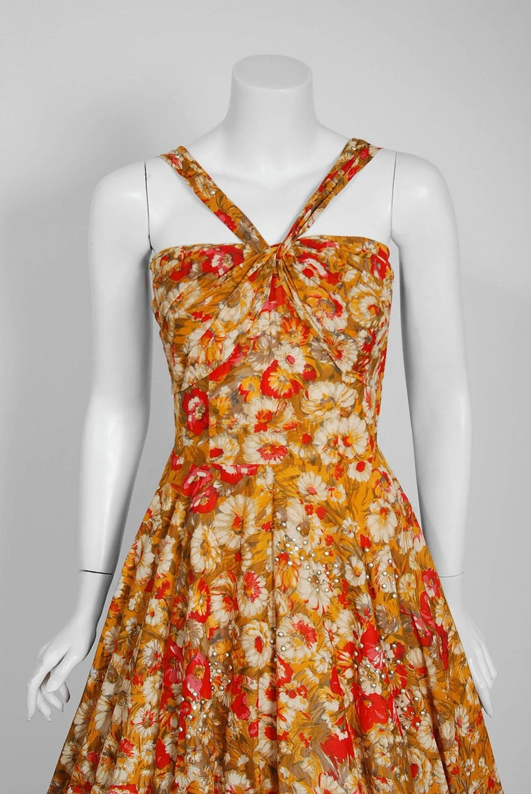 This gorgeous marigold daisies & red poppies floral print sundress by Aywon Originals is the perfect addition to any vintage wardrobe. The bodice has an alluring mock halter sculpted shelf-bust design. The hourglass nipped waistline is both ladylike