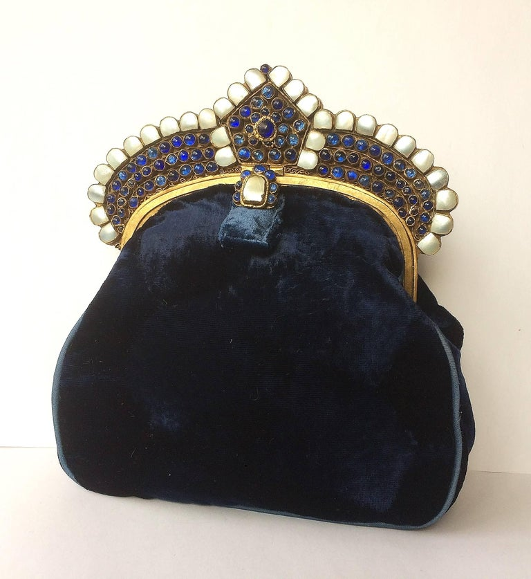 A sumptuous, rich, dark blue clutch bag from the 1920s, in a distinctive Moghul style, made from Royal blue silk velvet, most likely French in origin. The frame is made from base metal/brass, set with sapphire 'poured glass' cabuchons and mother of