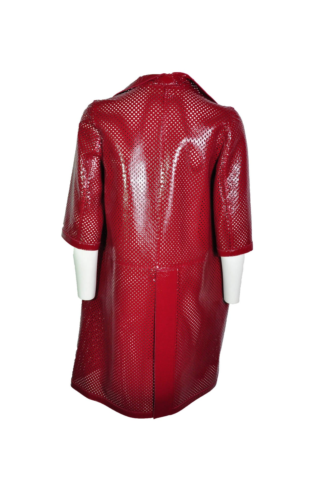 A chili red Marni short sleeves dust coat in perforated patent leather. Two seam side pockets.