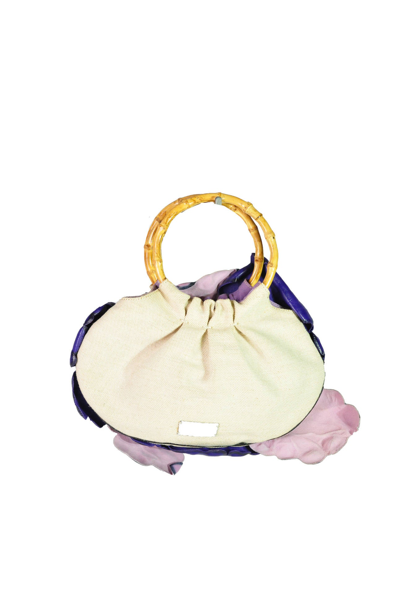 A very unique and rare Moschino mini canvas bag with double bamboo handles at top features with three large appliqued leather flowers in violet and pink colored leaves on front.  Fully lined in fabric with a zip interior pocket.