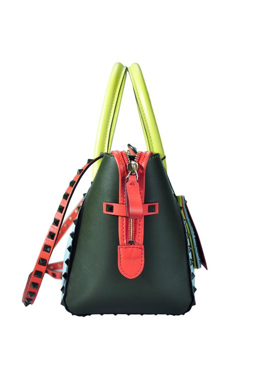 A Valentino Garavani Rockstud small trapeze tote bag in multi-colored calfskin, sky-blue, charcoal grey, red and yellow. Deep army lacquered studs with metal flip lock closure and zip fastening closure. Detachable studded strap, nappa lining, one