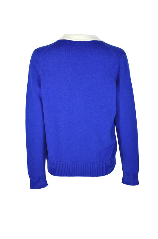 A V-neck 100% cashmere cardigan in blue/ecru color from Chanel 2016 Korean collection. Button fastenings through front with two front pockets.