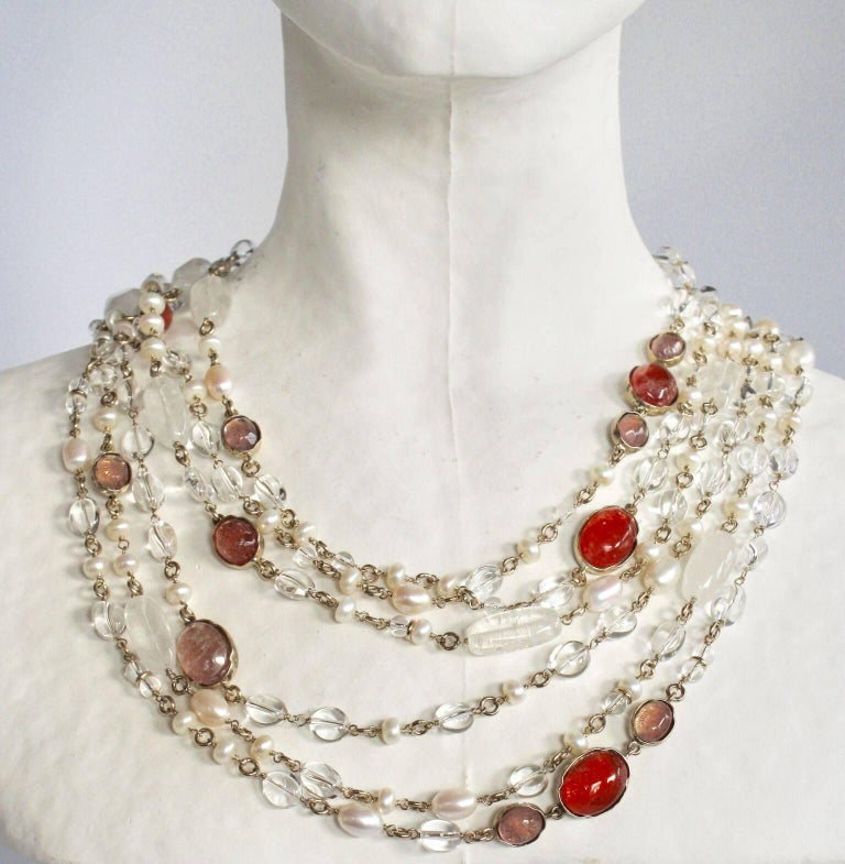 Triple row long necklace with hand painted rock crystals in pink/salmon surrounded by clear rock crystals and fresh water pearls. Necklace can be worn long or doubled and worn short to create a statement-making choker. From French design house