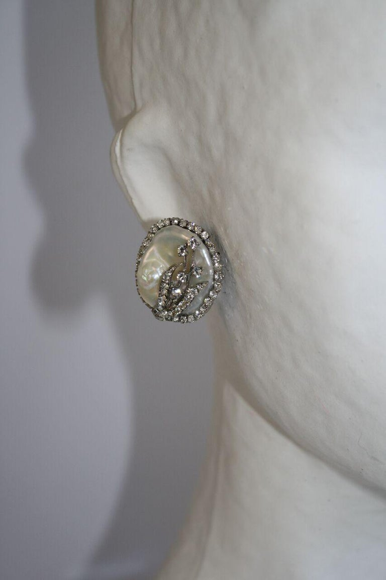 Pearl button clip earrings surrounded by Swarovski crystals from Mei's jewelry. Swarovski Crystal detailing on pearl is in the shape of floral bunch.