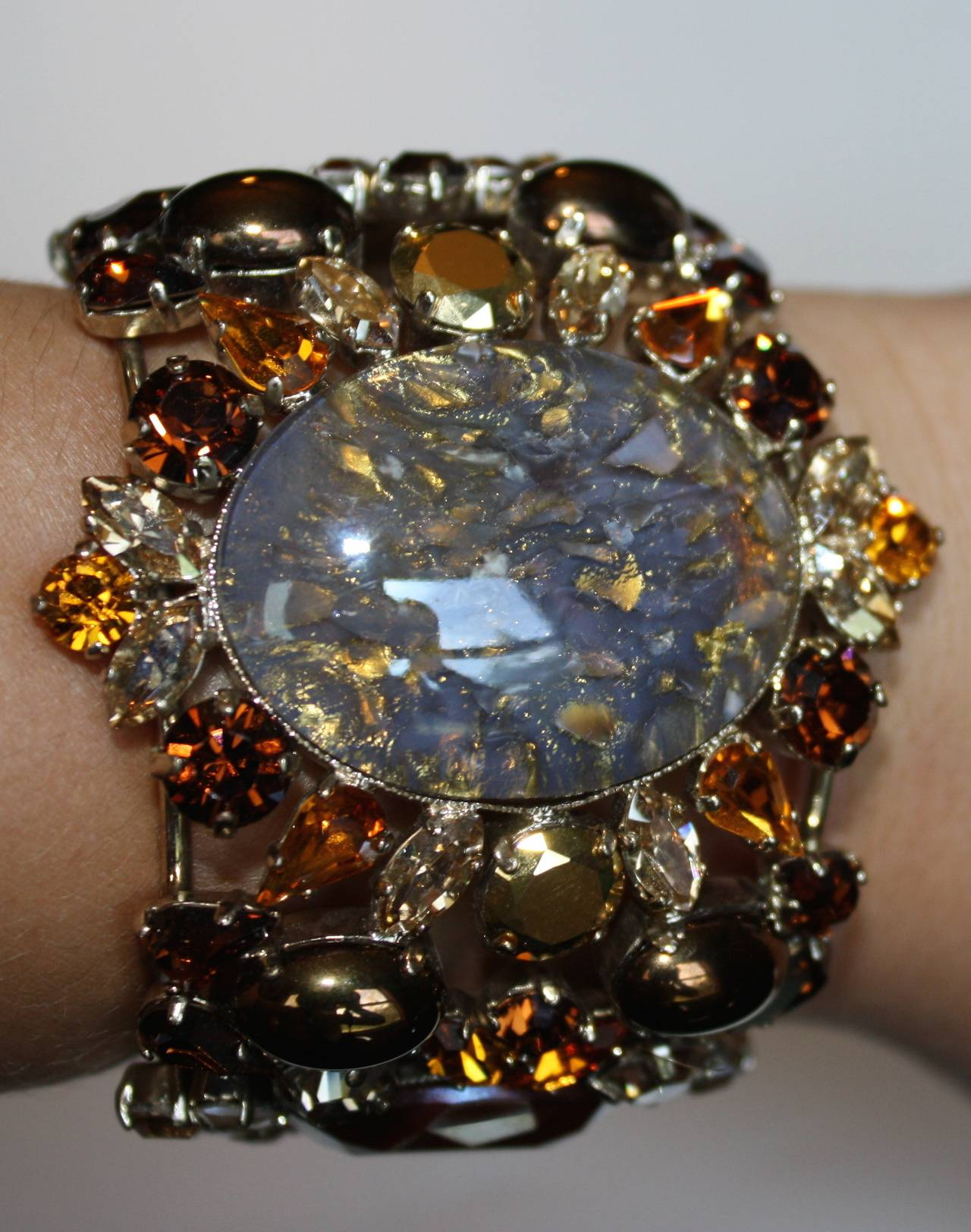Amber tone cuff bracelet from Philippe Ferrandis made with Swarovski crystals, glass cabochons, and gold plate. 