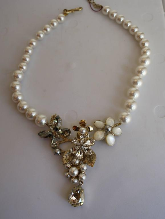 White glass pearls surround a magical mix of Swarovski crystal flowers and butterflies in this beautifully delicate necklace from Philippe Ferrandis. 