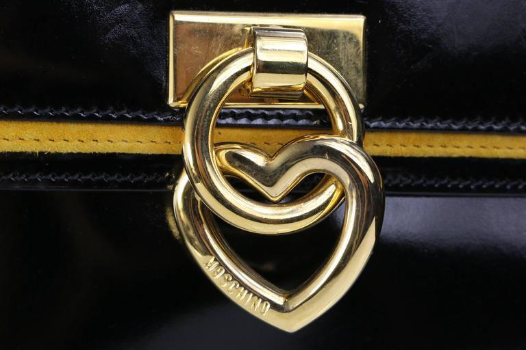 "- This beautiful and rare find late 80s vintage Moschino ""Peace&Love"" collection black leather handle bag with gold hue heart shape charm hardware and yellow suede trimming. Made in collaboration with the Italian fashion industry Redwall(Borhonese)."