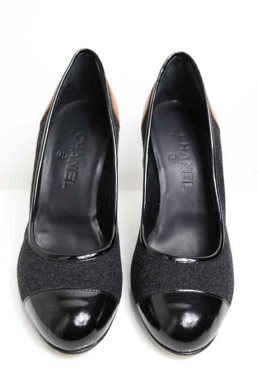 """- Chanel bi-colour black patent leather/grey wool pumps with written """"CHANEL"""" brown leather patch at back.   - Size 39 Italy.   - Length: 22cm I Heels: 16cm."""