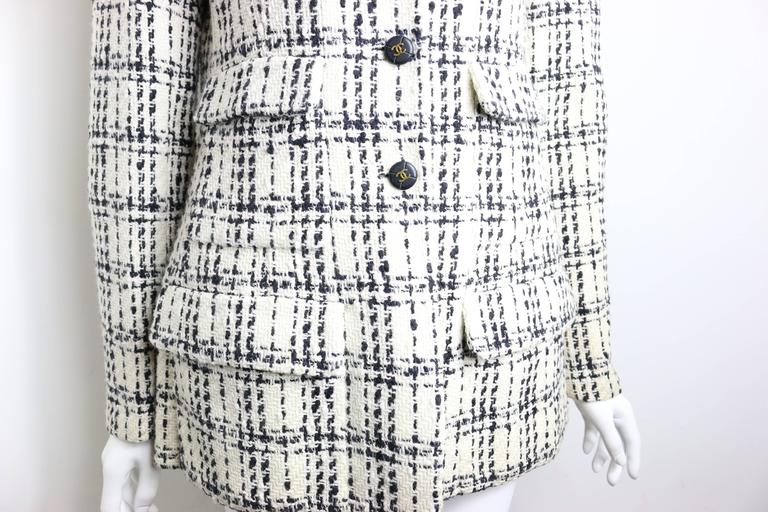 - Vintage Chanel classic black and white plaid pattern tweed cotton blend jacket.   - Boxy cut with slightly padded shoulder.   - Notched lapel.   - Triple button-front closure.   - Four Front flap pockets.   - Button detail at cuffs.  - Fully